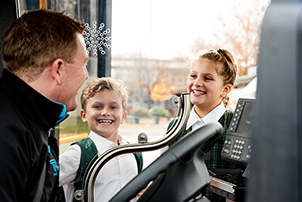 Kids greeting the bus driver as they catch the bus to school.