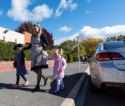 A mother walks with her children from the school car park into school.
