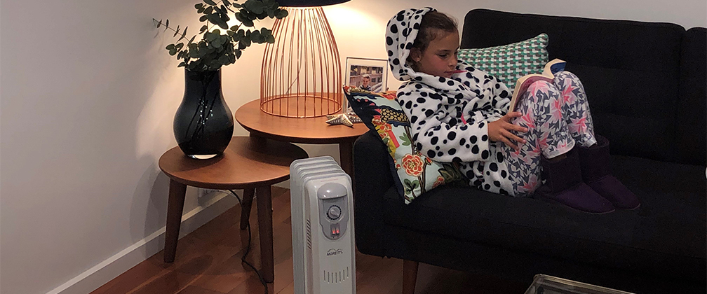 A young girl sitting on the couch by the portable heater.
