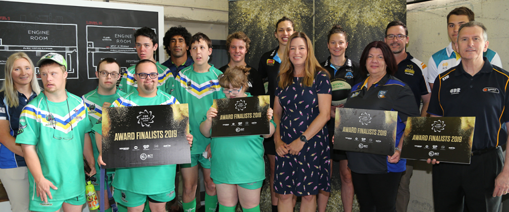 Standing for a photo at the Canberra Glassworks Score Raiders players (in green uniforms), Sia Soliola (Canberra Raiders), Kye A'Hern (Downhill Mountain Biking), Marianna Tolo (UC Capitals), Yvette Berry MLA, Kelsey Griffin (UC Capitals), Marie Hart (Indoor Cricket), Dan McKellar (Brumbies Rugby), Nicholas Taylor (Waterpolo), Phil Brown (Basketball)