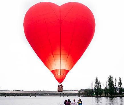 Boat on a lake under heart-shaped hot air balloon.