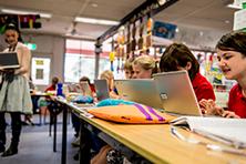 Teacher and children on laptops