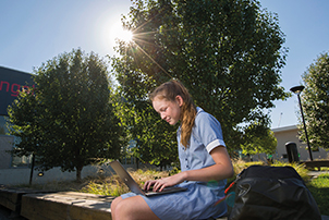 School student sitting using laptop in outdoor area
