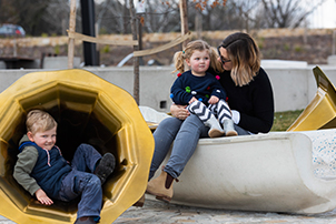 A family interacting with the new artwork at Henry Rolland Park.