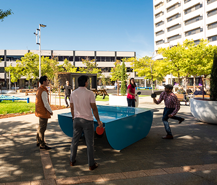 A group of people play ping pong at the new Woden Town Square.