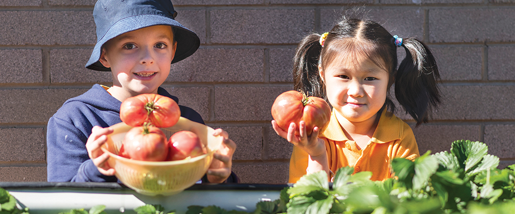 Two Ngunnawal Primary students holding fresh produce.