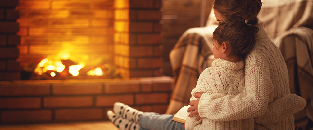 A mother and daughter at night sitting by a wood fire in a home.
