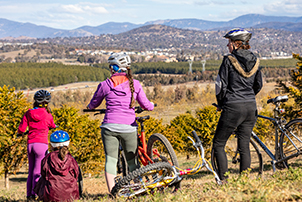 Women and children riding their bikes outside at the National Arboretum Canberra