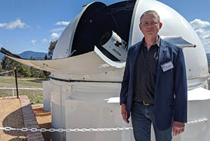 Geoff McNamara standing in front of the MSATT Telescope on a sunny day.
