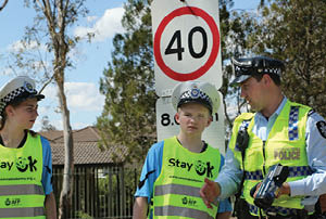 Child with police officer at speed limit sign.