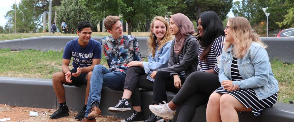 Six students sitting outside.