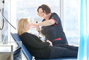 Medical professional tending to woman in a chair.