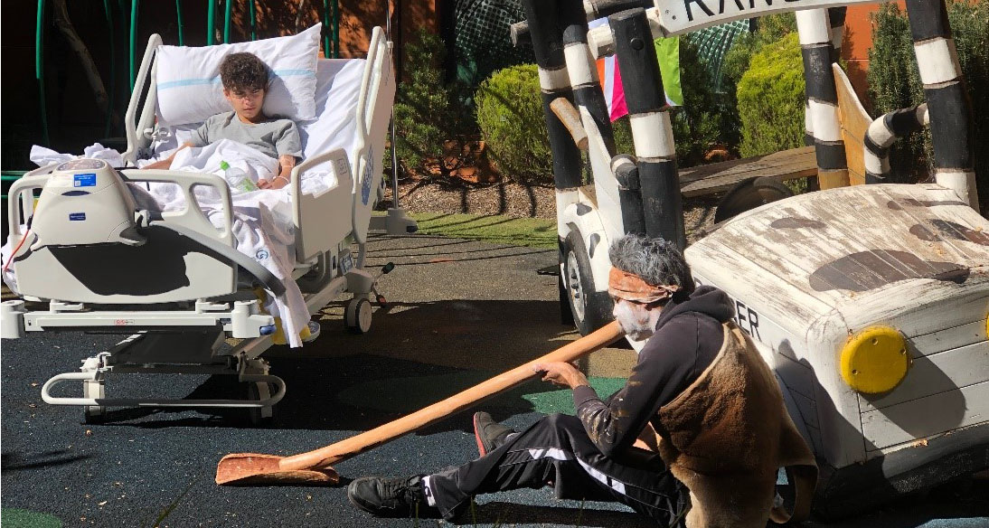 Wiradjuri man, Roy Peterson, playing the digeridoo for a young patient.