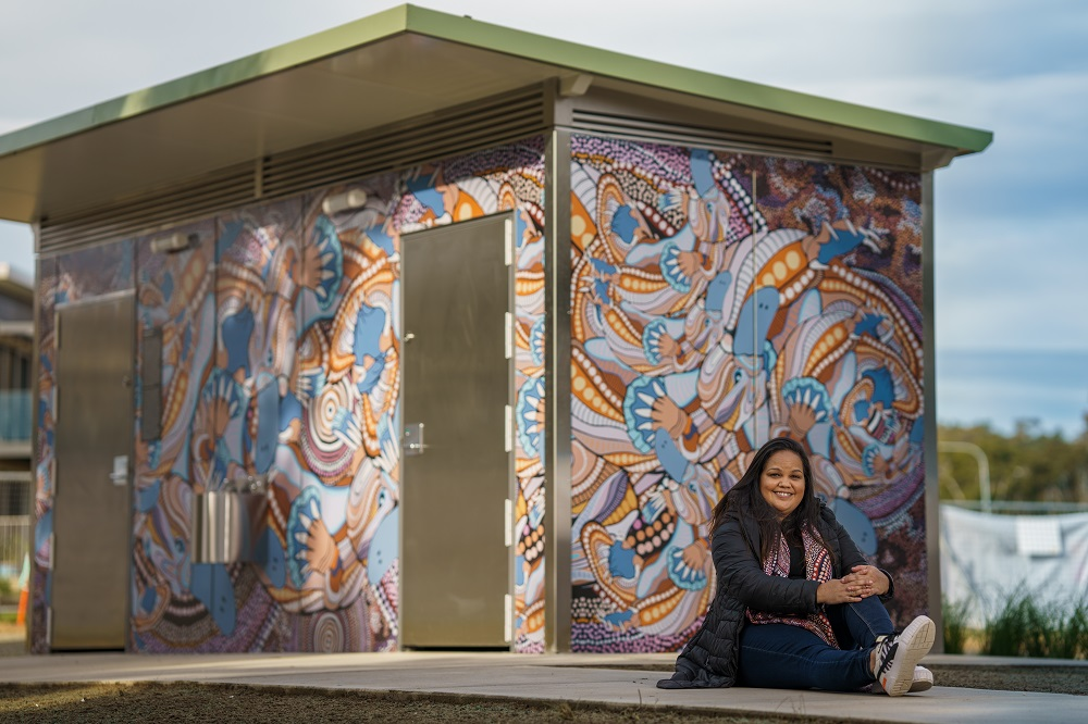A woman sits in front of a newly painted public toilet block