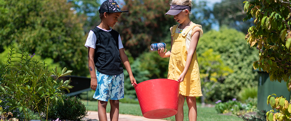 A boy and a girl holding a bucket full of recycling