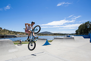 Teenage boy on bike jumping from skate park ramp