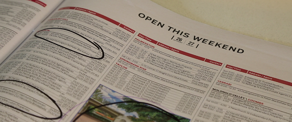 A person looking at a open house guide for Canberra.