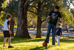 A family kicking a soccer ball in a park in Canberra