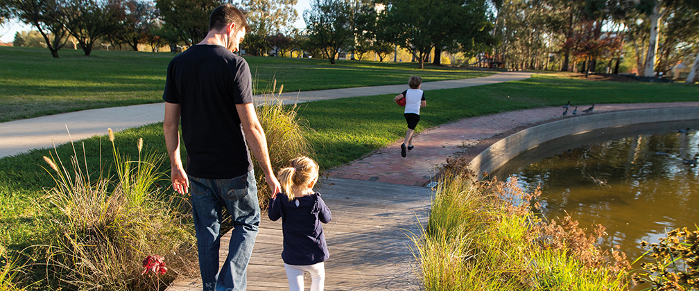 A family walking through a park in Canberra