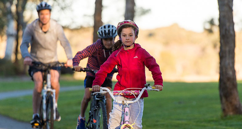 Young girl riding her bike with father and brother following behind in their bikes