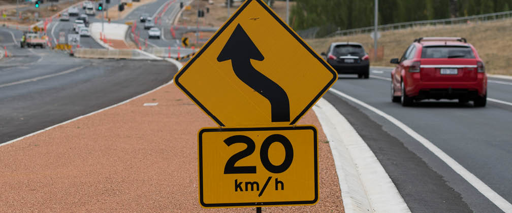 20km/h speed sign in centre of image with cars driving in the background