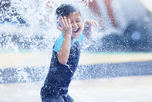 A young boy splashing around in a pool.