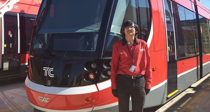 Kenneth standing in front of a light rail vehicle